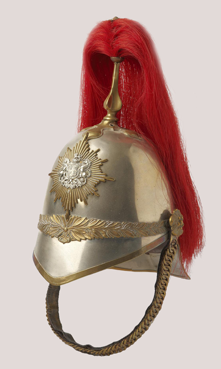 The helmet, circa 1880, is of white metal construction. Across the front seam a decorative gilt band of olive leaves and a band of oak leaves conceals the rear seam. A plain gilt chain backed with leather and attached to the helmet with gilt rosettes. The plume is attached to the helmet through a gilt spike resting on a plain quatrefoil.