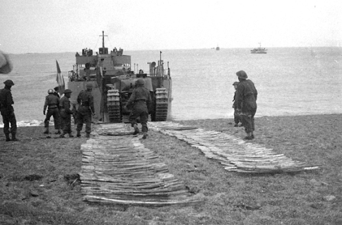 Churchill tanks of The Calgary Regiment taking part in a series of exercises (Yukon I, 11/12 and Yukon II, 22/23 June 1942) that were held at the tiny fishing harbour of West Bay on the coast near Bridport, Dorset. In this photo, soldiers of the Royal Canadian Engineers, have rolled out bundles of chespaling tracks to enable the disembarking tanks to cross the beach. Source: Authors' collection.