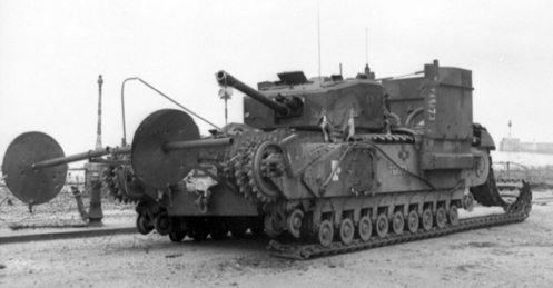 "T68173 Cougar, a Churchill Mk III of No. 13 Troop, ""C"" Squadron, The Calgary Regiment, one of the five tanks fitted with the ""Beach Track Laying Device,"" for the landings at Dieppe on 19 August 1942. Having only jettisoned part of its beach track laying device, the remains of it are clearly visible on her front. Notice how the two short brackets carried the spindle, and that the inside and outside 3 foot diameter, 14 gauge metal disc shields, that prevented the chespaling from fouling the brackets and spindle, have closed up on themselves. Note also, the remains of the rigid conduit, on her right side, that had to be added for the protection of the wiring for the electrically fired small explosive charges, that released the rolls, and for those that jettisoned the whole device. Source: Authors' collection."