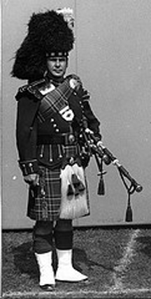 An undated photo of a piper. His sporran cantle displays a badge while the remainder of his accoutrements are plain.