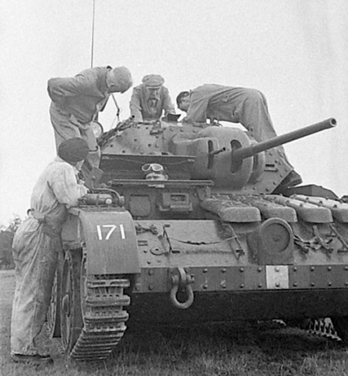 "Front view of a Covenanter IV, of Headquarters, 1st Canadian Army Tank Brigade, armed with the 2-pounder Ordnance Quick Firing gun, and co-axial .7.92-millimetre Besa machine gun. The barrel of the anti-aircraft/ground defence .303-inch Bren light machine gun, connected to the Lakeman anti-aircraft mount, can be seen, just above the driver's right shoulder, and behind it, the spotlight, which was standard on British tanks of the period, and in the case of the Covenanter, was mounted on the right-side of the turret. The number '171,' which appears on the right-front track guard, is the Arm of Service marking, by which vehicles belonging to Headquarters, 1st Canadian Army Tank Brigade, were identified, from August 1941 to May 1943. This Arm of Service marking, consisted of the number '171,' in white, centrally located on a horizontally divided blue over brown coloured square. The white square, directly below the headlamp housing, is the centre portion, of the 'Armoured Fighting Vehicle Recognition Sign,' which was used as a form of ""National Identification"" marking for British and Canadian armoured fighting vehicles, of the period. It consisted of a 10-inch high by 18-inch wide rectangle, which was divided vertically into three 6-inch wide red/white/red strips. Source: MilArt photo archive."