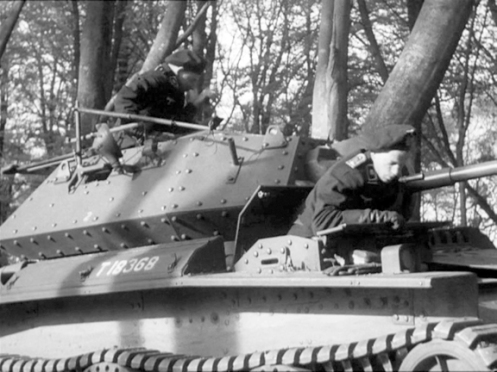 T18368, a Covenanter I, which was issued to Headquarters, 1st Canadian Army Tank Brigade, on 5 August 1941, taking part in the filming of a British Military Training Film, entitled 'Ten Tips for Tackling Tanks,' in the fall of 1941, for which the crew is dressed as a German tank crew. The Covenanter driver's compartment was notably cramped, as is illustrated here, note, there isn't too much room between the driver, who is leaning on the folded down hinged front section, and the hinged two-piece rear section, of his hatch. Note the short pipe, on the turret side, just behind the driver, this was for the barrel of the anti-aircraft/ground defence .303-inch Bren light machine gun, to rest on when connected to its Lakeman anti-aircraft mount (a portion of which is visible), when not in use. The number '2,' which appears midway along the turret side, indicates, that this is the number two tank of brigade headquarters (see the next caption for details). Source: authors' collection.