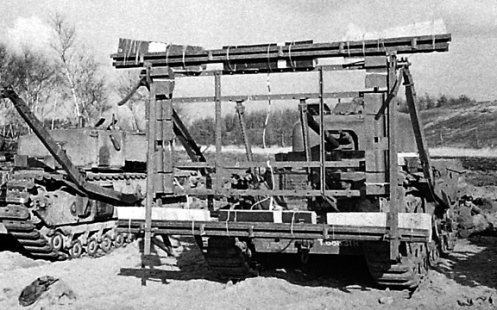 "Front view of a Churchill Mark IV tank, of The Calgary Regiment, at Whitley, Surrey, fitted with the ""Onion"" explosive device. In this case, the high explosive charges in boxes are attached three along the top and three along the bottom of the outer face of the framework. Note also, the two outward facing legs, attached to either corner of the top of the framework, which would enable the device to be hung from an obstacle such as a wall or bunker. Source: MilArt photo archive."