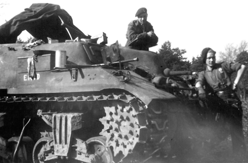 ENID, a Kangaroo of the 1st Canadian Armoured Personnel Carrier Regiment, showing a closer view of examples of the crescent shaped 'tarp/bivouac' supports, the secondary .30-calibre Browning machine gun (with the feed tray) mounted in the front of the turret ring, with its barrel pointing to the right, the track extended end connectors on the outside edge of the track, and the later style of bogie assembly, with the return roller mounted on a trailing arm behind the bogie assembly. Source: 1 CACR Association & Archive