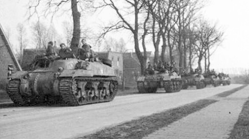 "No. 1 Troop, ""A"" Squadron, 1st Canadian Armoured Personnel Carrier Regiment, carrying infantrymen of ""B"" Company, The Royal Hamilton Light Infantry, 4th Canadian Infantry Brigade, advancing on Groningen, Holland, on the morning of 13 April 1945. Source: 1 CACR Association & Archive"