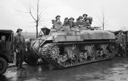 "A 'Ram' Kangaroo armoured personnel carrier of ""A"" Squadron, 49th Armoured Personnel Carrier Regiment, carrying infantrymen of the 4th Battalion, Dorsetshire Regiment, 130th British Infantry Brigade, on the outskirts of Ochtrup, Germany, 3 April 1945, prior to the liberation of Enschede, Holland. Source: Imperial War Museum  (BU 2956)"
