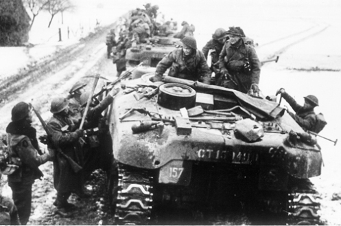 """Infantrymen of the 2nd Battalion, Devonshire Regiment, of 131st British Infantry Brigade, loading onto 'Ram' Kangaroo armoured personnel carriers of """"B"""" Squadron, 1st Canadian Armoured Personnel Carrier Regiment, near Dieteren, Holland, on 15 January 1945, during Operation BLACKCOCK. Note that the crew of the 'Kangaroo' in the foreground has left their pioneer tools strapped in place on the rear deck, common practice within the Regiment was to remove these, so that their infantry passengers wouldn't make off with them for their own use. Source: Bovington Tank Museum (BTM 2293-A5)"""