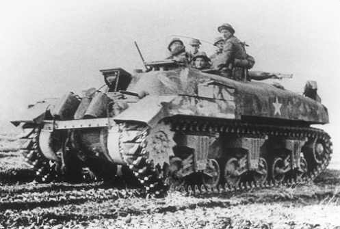 """A 'Ram' Kangaroo armoured personnel carrier of """"A"""" Squadron, 1st Canadian Armoured Personnel Carrier Regiment, lifting infantrymen of the Royal Winnipeg Rifles, 7th Canadian Infantry Brigade, in a thrust along the Cleve to Calcar road (Germany), on 16 February 1945, during Operation VERITABLE. Note the forward facing secondary .30-calibre Browning machine gun mounted in the turret ring, with its barrel pointing skyward. Source: MilArt photo archives"""