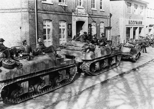 """BUCKSHEE and another 'Ram' Kangaroo armoured personnel carrier of """"B"""" Squadron, 1st Canadian Armoured Personnel Carrier Regiment, with infantrymen of """"A"""" Company, The Argyll & Sutherland Highlanders of Canada (Princess Louise's), 10th Canadian Infantry Brigade, in Werlte, Germany, on 11 April 1945. Note the track extended end connectors on the outside edge of the right track, of both 'Kangaroos', and also the position of the secondary .30-calibre Browning machine gun mounted in the turret ring. Source: MilArt photo archives"""