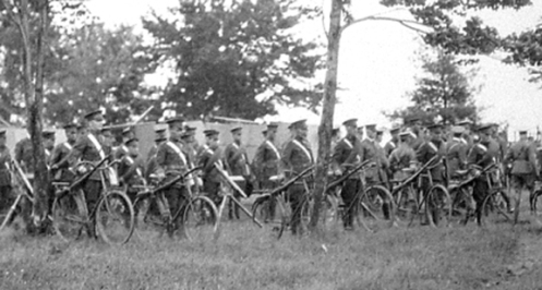 Line-up of cyclists parading next to the Autocars purchased by Brutinel. MilArt photo archives